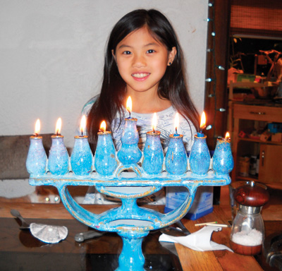 Abby lighting the menorah